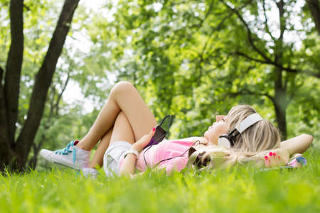good life: Young woman listening to music while lying down on grass Stock Photo