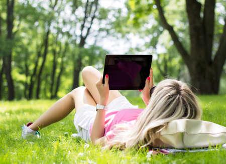 persona leyendo: Relajado joven con tablet PC al aire libre Foto de archivo