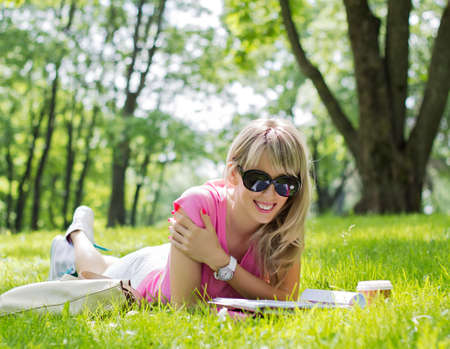 Happy young woman reading magazine in park photo