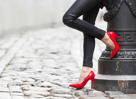 black girl nude: Woman wearing black leather pants and red high heel shoes in old town