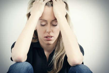 mujer decepcionada: Mujer tensionada que se sienta en el suelo y con las manos a la cabeza Foto de archivo