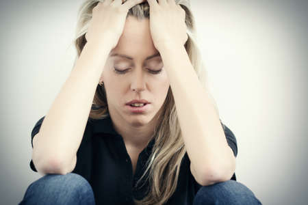Stressed woman sitting on ground and holding hands to head