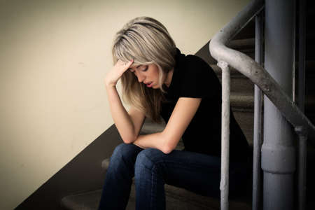 Young unhappy woman in depression sitting on stairs