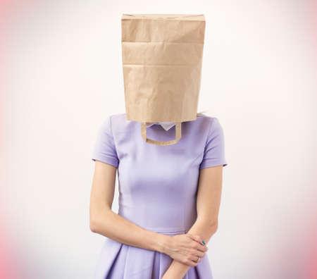젊은여자가 그녀의 머리 위에 종이 봉지와 함께 스톡 콘텐츠