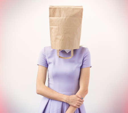 Young woman with paper bag over her head   Stock Photo