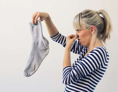 dirty clothes: Woman holding dirty socks with her nose closed