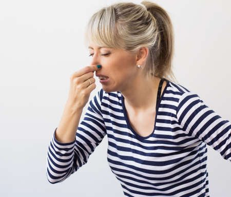 unpleasant smell: Woman disgusted by bad smell holding her nose Stock Photo