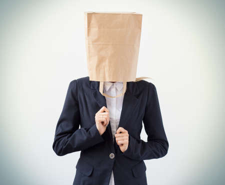 apathetic: Young businesswoman with paper bag over her head