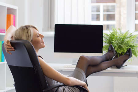 work life balance: Relaxed woman enjoying successful day at work   Stock Photo