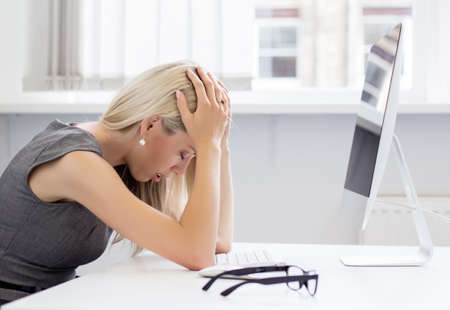 frustrated: Overworked and frustrated young woman in front of computer