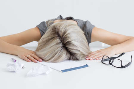 Overworked and tired young woman sleeping on desk Stock Photo