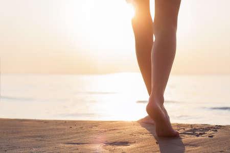 夕暮れ時のビーチを歩いて女性
