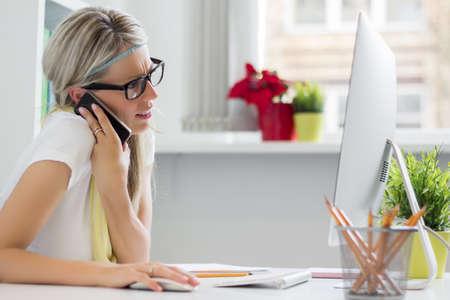 Jonge creatieve vrouw praten over de telefoon in het kantoor