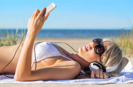 Young woman listening to music on headphones on the beach photo