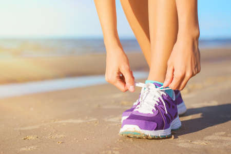 Woman wearing running shoes on the beach
