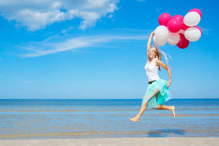 expressive mood: Happy girl holding bunch of colorful air balloons at the beach