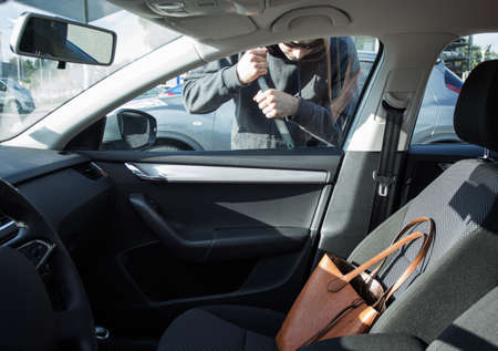unattended: Thief breaking in a car Stock Photo