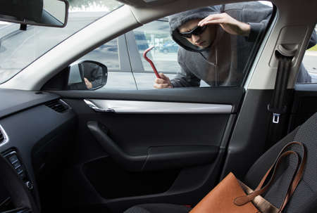 Thief is looking for unattended valuables left in a car 写真素材