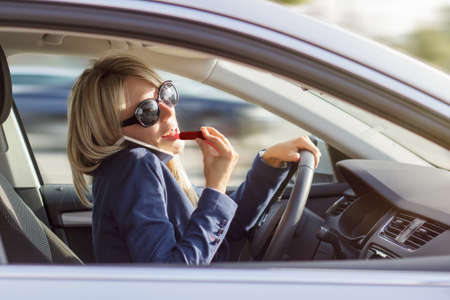 Busy woman manage to talk on phone and do makeup while driving a car