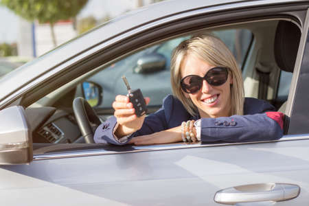 car rental: Happy young woman showing her new car keys