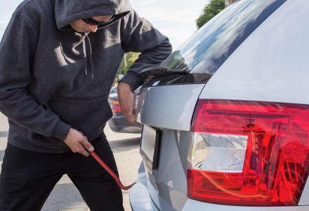 unattended: Thief breaking car rear door lock Stock Photo