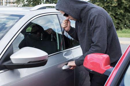 Thief breaking car door lock photo