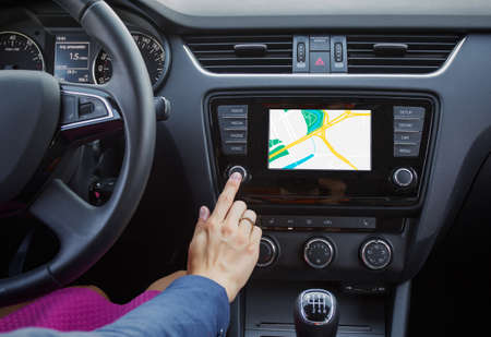 Woman using navigation system while driving a car photo