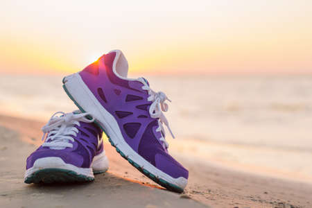 Pair of running shoes on the beach at sunset
