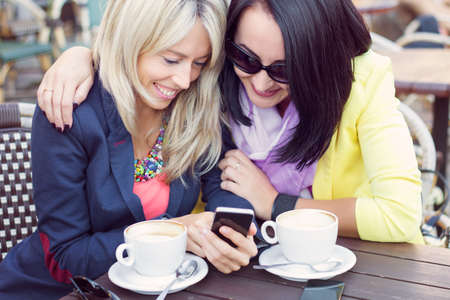 Two female friends sitting in cafe and viewing photos on mobile phone photo