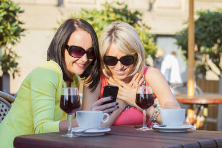 Two attractive women sitting in cafe and viewing photos on mobile phone photo
