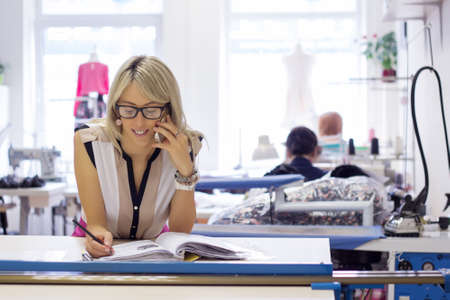 Trabajadores por cuenta propia mujer joven que toma pedidos de los clientes por teléfono Foto de archivo