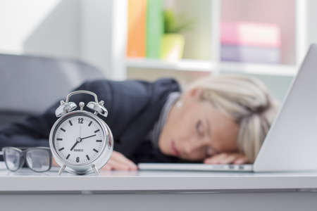 Exhausted woman sleeping in front of computer photo
