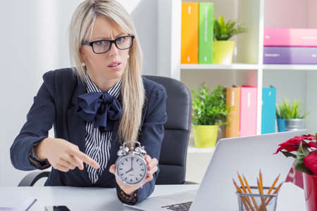woman with clock: Frustrated business woman is angry about being late at work