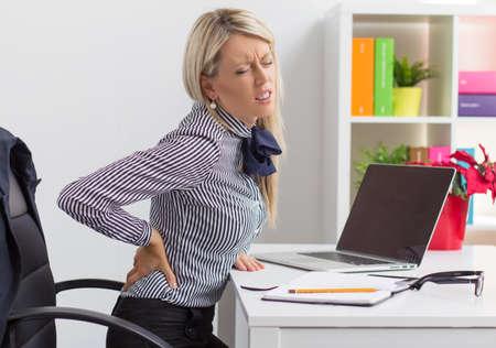 Jonge vrouw met pijn in de rug tijdens de vergadering op bureau in het kantoor