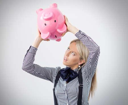 여자는 돼지 저금통에서 돈을 얻으려고 노력