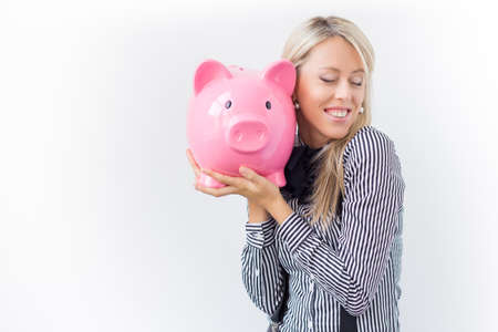 finance girl: Happy woman holding pink piggy bank