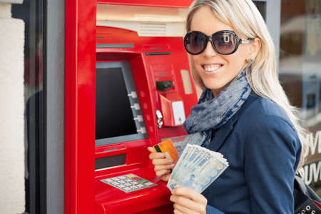 withdrawing: Beautiful young woman showing cash after withdrawal from ATM