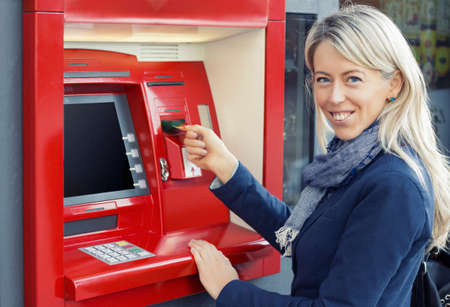 withdraw: Happy woman using ATM to withdraw money