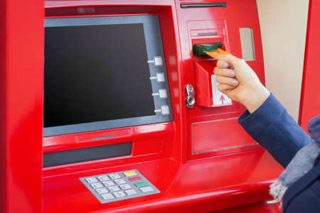 inserting: Woman inserting credit card into ATM to withdraw money