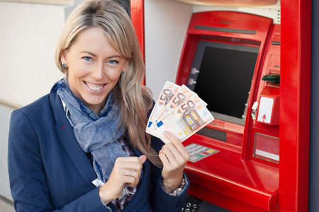 automatic machine: Happy woman withdrawing cash from ATM