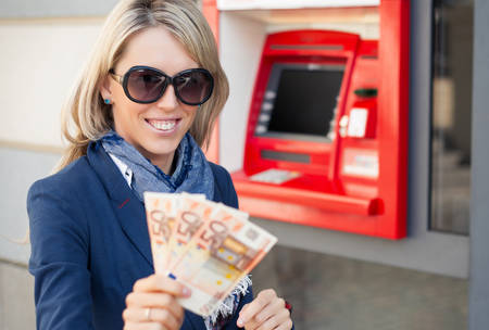 withdrawing: Happy woman withdrawing money from ATM Stock Photo