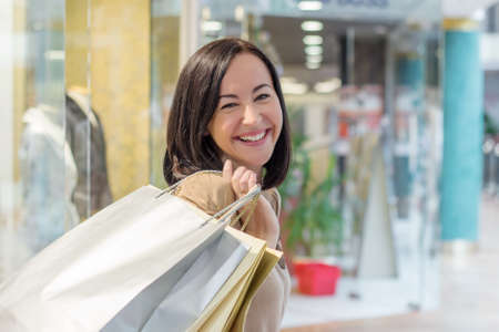 woman holding money: Young woman smiling with shopping bags over the shoulder