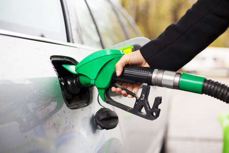 refuel: Close-up photo of hand holding fuel pump and refilling car at petrol station Stock Photo