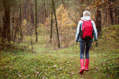 Woman hiking in forest during rainy autumn season photo
