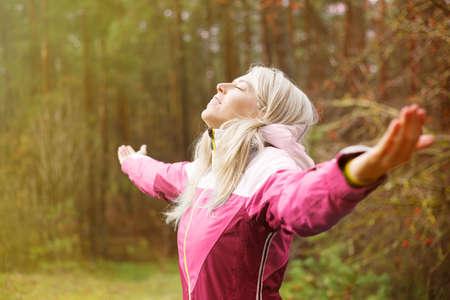 Woman breathes fresh air outdoors in autumn photo