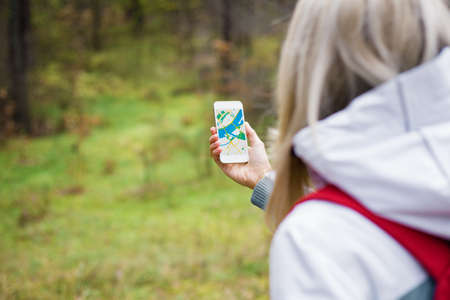 navigating: Woman geocaching in forest and using map app on smartphone Stock Photo