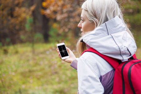 Woman checking compass app on her smartphone