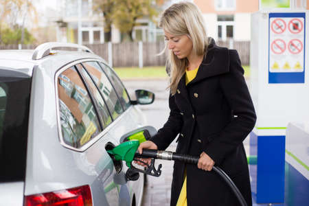 refilling: Young woman refilling petrol in gas station