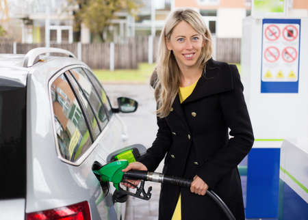 refilling: Young woman refilling car in gas station