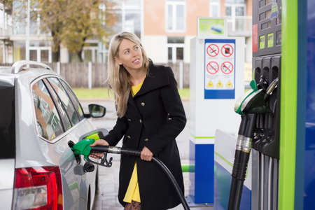 refuel: Woman refilling car with fuel Stock Photo